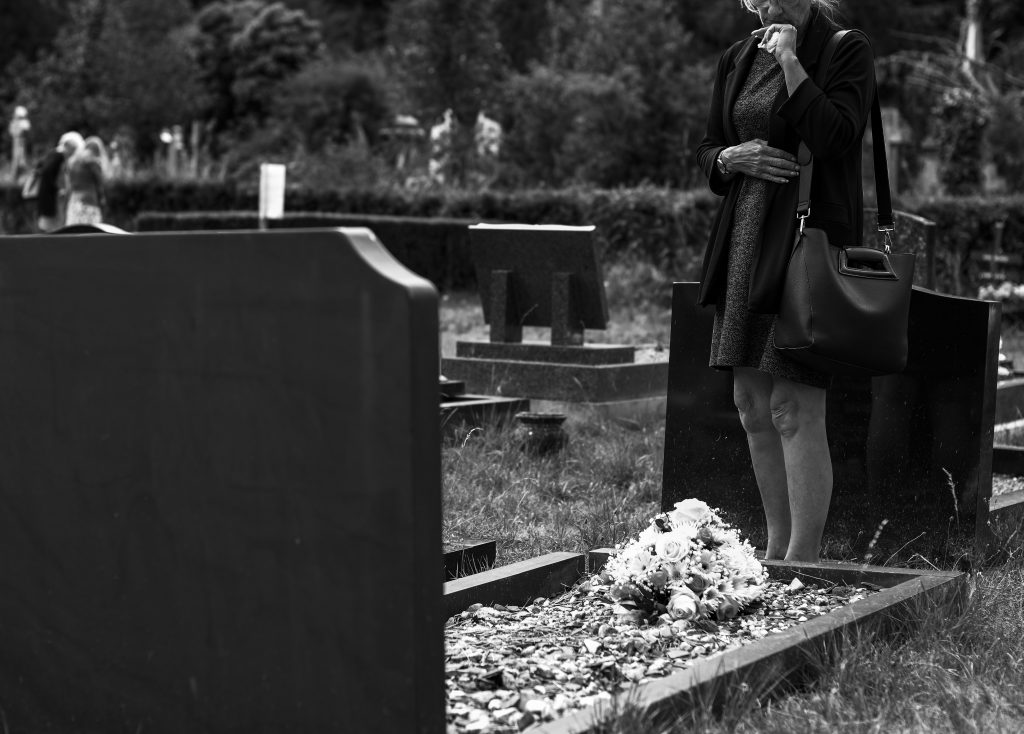 Woman standing in front of a grave site in black and white.