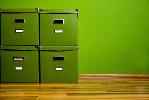 Green bankers boxes on a parquet floor