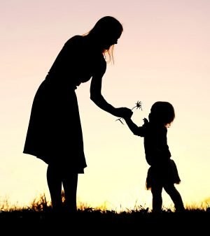 Woman giving flower to child at sunset