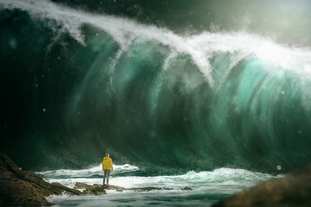 Photo of man in yellow rainjacket standing at base of tsunami
